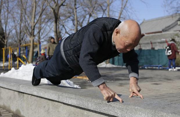 Chinês de 82 anos foi flagrado fazendo flexões usando apenas dois dedos de cada mão (Foto: Jason Lee/Reuters)