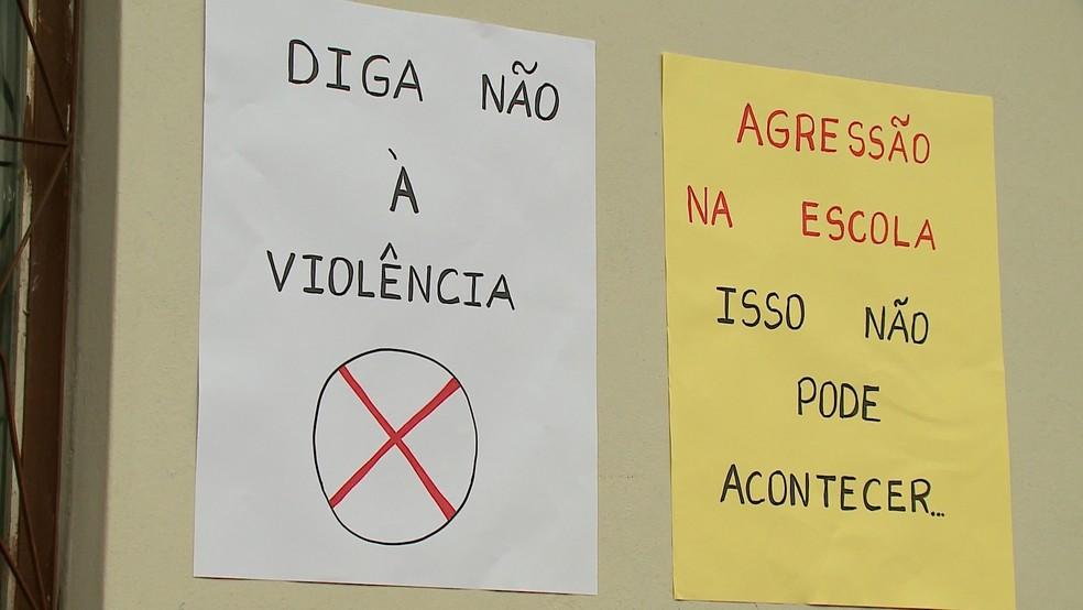 Cartazes fixados nas paredes da escola pedem o fim da violência (Foto: Reprodução RBSTV)