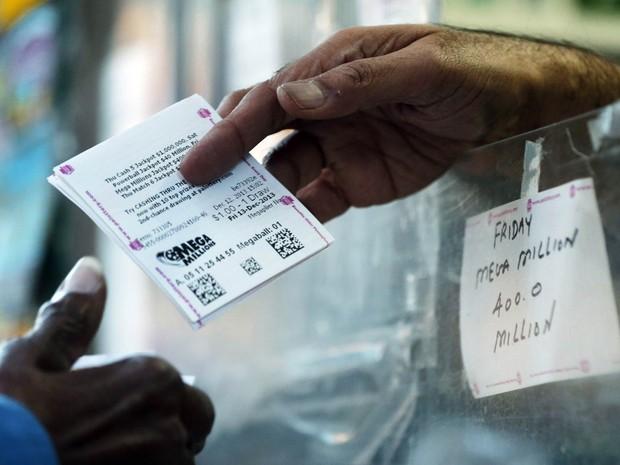 Mulher compra um tíquete da loteria Mega Millions em uma banca de revistas na Filadélfia, nos EUA. Espera-se que o sorteio deste sexta-feira (13) renda um prêmio de US$ 400 milhões, que seria o quinto maior da história no país. (Foto: Matt Rourke/AP)