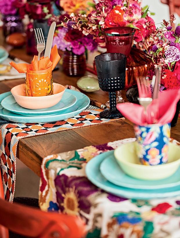 Uma ideia simples e com um efeito surpreendente é misturar pratos, tigelas e taças de diferentes cores. Use copinhos decorados e com texturas diferentes para acomodar os talheres. Jogos americanos estampados finalizam a produção e trazem mais charme à mesa.  (Foto: Elisa Correa/Editora Globo)