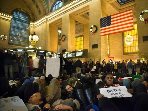Manifestantes deitam no piso da Estação Central de Nova York. (Foto: John Minchillo / AP Photo)