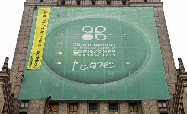 """Integrantes do Greenpeace penduraram nesta quinta-feira (21) uma faixa no Palácio da Cultura e Ciência de Varsóvia, capital da Polônia, com os dizeres """"Salve o Ártico e liberte nossos ativistas"""". O objetivo é chamar a atenção para a prisão dos integrantes da ONG na Rússia. O protesto coincide com a retirada das ONGs da COP 19 (Foto: Kacper Pempel/Reuters)"""