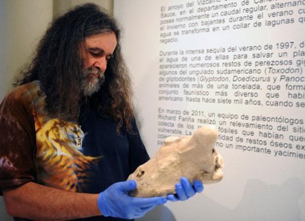 Paleontologista Ricardo Fariña segura fóssil encontrado no Arroio de Vizcaino, em Montevidéu (Foto: Miguel Rojo/AFP)