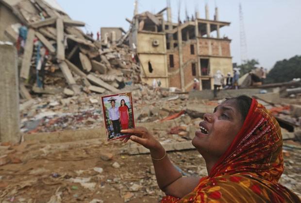 Mulher mostra foto do marido que está desaparecido (Foto: Kevin Frayer/AP)