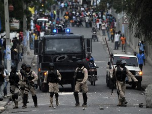 Polícia haitiana caminha em meio ao protesto em Porto Príncipe neste domingo (24) (Foto: Hector Retamal/AFP)