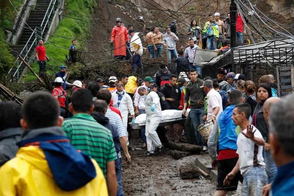 Equipe de resgate carrega corpo após deslizamento em Manizales, na Colômbia  (Foto: AFP)