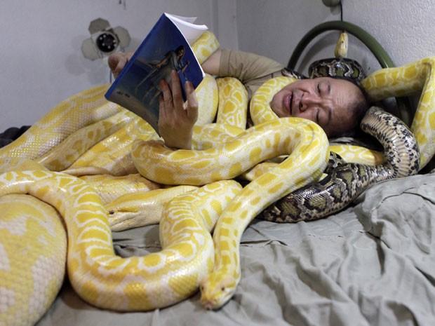 O proprietário de um zoológico Emmanuel Tangco lê um livro com cobras no zoológico de Malabon, em Manila, nas Filipinas, neste domingo (3). O Ano Novo Lunar começa no dia 10 de fevereiro neste ano e marca o Ano da Cobra (Foto: Erik De Castro/Reuters)