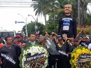 Trabalhadores protestam vestidos de preto e com coroas de flore representando luto pela fala de salário. Um caixão e o boneco gigante de um trabalhador também foram levados para o ato (Foto: Cacyone Gomes / TV Globo)