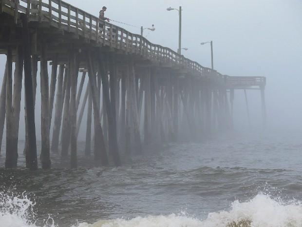 Homem pesca em píer sobre mar revolto em Nags Head, na Carolina do Norte, nesta quinta-feira (3) (Foto: Mark Wilson/Getty Images North America/AFP)