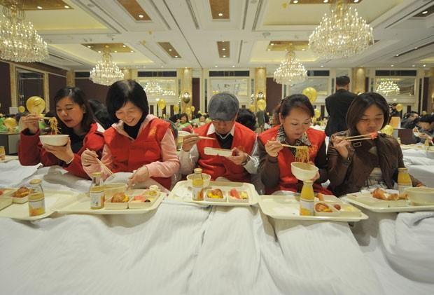 Grupo estabeleceu um novo recorde mundial para o maior número de pessoas tomando café da manhã na cama (Foto: Jia Ru/AFP)