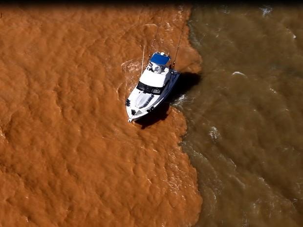 Barco passa por divisa entre lama e mar, em Regência, Linhares (Foto: Marcello Lourenço/ Arquivo Pessoal)