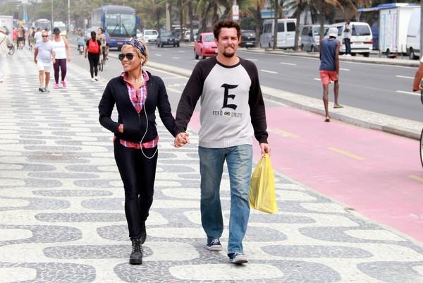 Felipe Dylon e Aparecida Petrowky caminham juntinhos em praia do Rio