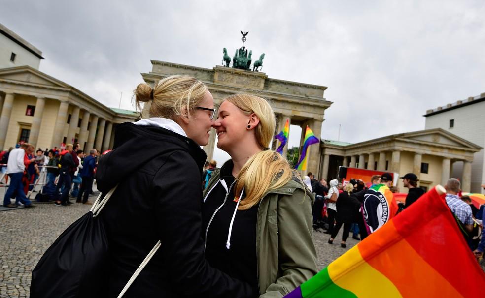 Mulheres se abraçam em manifestação em frente ao Portão de Brandenburg, em Berlim, nesta sexta-feira (30) (Foto: Tobias Schwarz / AFP)