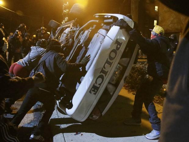 Manifestantes reviram uma viatura policial em Ferguson, Missouri, no segundo dia seguido de protestos após um júri inocentar o policial que matou um adolescente negro que não estava armado (Foto: Jim Young/Reuters)