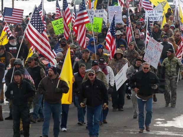 Manifestantes marcham neste sábado (2) em apoio a uma família de fazendeiros que enfrenta pena de prisão por provocar incêndios em Burns, no estado do Oregon (Foto: Les Zaitz/The Oregonian via AP)