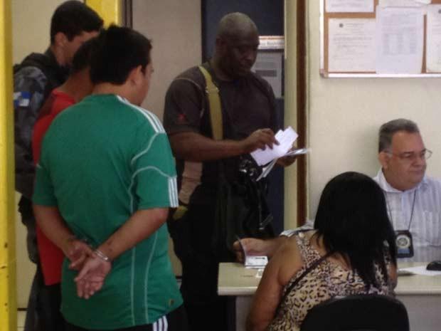 De costas, de camisa verde, Playboy, que seria chefe do tráfico do Caju (Foto: Cristiane Cardoso/G1)