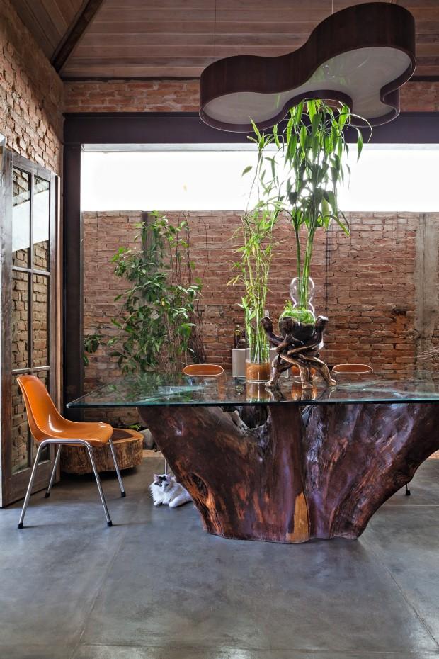 Mesa de tronco de madeira com cadeira laranja (Foto: Lufe Gomes / Editora Globo)