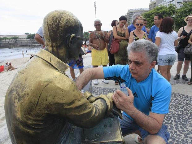 O comerciante Herbert Parente, morador do bairro de Copacabana, limpa voluntariamente a estátua de Carlos Drummond de Andrade, que foi pichada por vândalos na noite de Natal. (Foto: Maíra Coelho/Agência O Dia/Estadão Conteúdo)