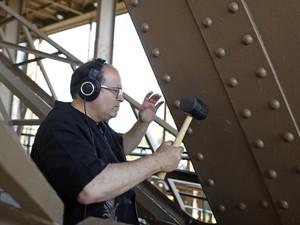 Músico de Nova York Joseph Bertolozzi usa marreta para produzir música na Torre Eiffel, em Paris (Foto: Reuters/Benoit Tessier)