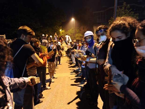 Manifestantes carregam pedras para a construção de uma proteção durante confrontos com a polícia entre Taksim e Besiktas em Istambul (Foto: Bulent Kilic/ AFP)