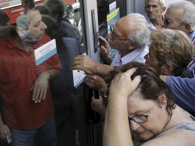 Pensionistas aguardam em frente a uma agência fechada do Banco Nacional da Grécia, na esperança de receberem suas pensões, e discutem com um funcionário do banco em Iraklio, na ilha de Creta (Foto: Stefanos Rapanis/Reuters)