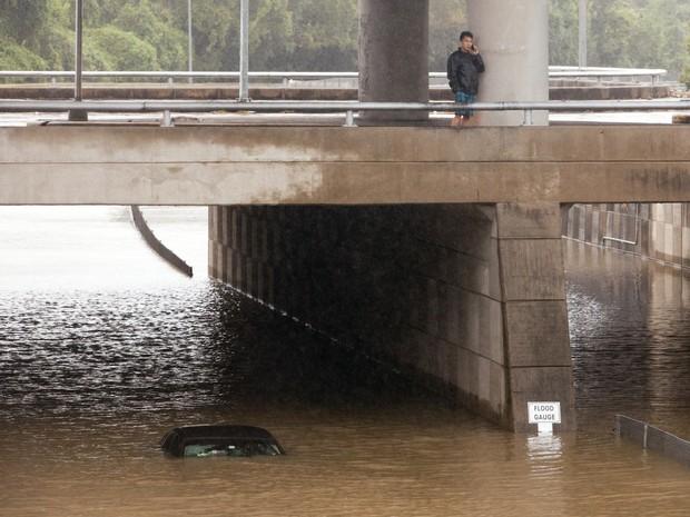 Motorista do Uber fala ao celular perto de seu carro inundado por enchente em Houston, Texas, neste domingo (25) (Foto: Reuters/Daniel Kramer)