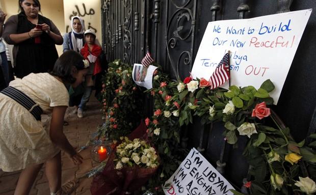 Garota coloca flores no portão do consulado dos EUA em Benghazi. O embaixador Chris Stevens e outros três funcionários morreram no ataque.  (Foto: AP)