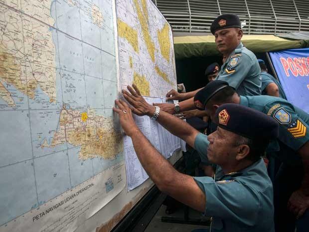 Oficiais da Força Aérea da Indonésia mostram mapas da área de busca do avião desaparecido. (Foto: Juni Kriswanto / AFP Photo)