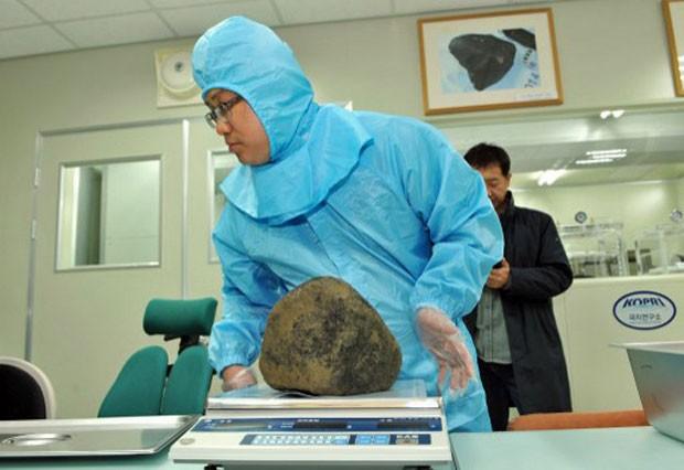 Pedaço de meteorito que caiu na Coreia do Sul no começo deste mês é pesado em laboratório (Foto: Korea Polar Research Institute/AFP)