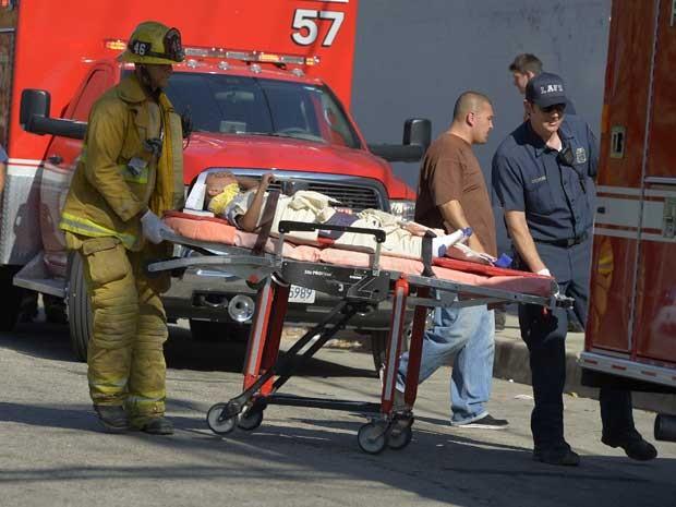 Criança é transportada por bombeiros para atendimento médico. (Foto: Mark J. Terrill / AP Photo)