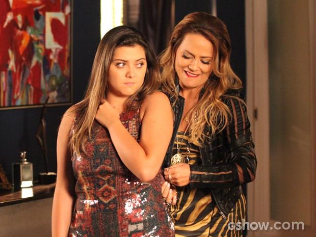 Ela muda de ideia e até tenta ajudar a menina a vestir a roupa... Mas naõ entra (Foto: Carol Caminha/TV Globo)