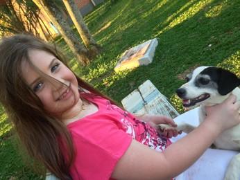 Pietra acaricia um dos 13 cães na fazenda da família (Foto: Claudia Gasparin/Arquivo Pessoal)