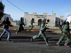 Pessoal de segurança israelense corre para sinagoga atacada por dois homens. (Foto: Ronen Zvulun / Reuters)
