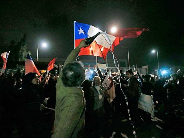 Chilenos se reúnem em frente ao hospital para celebrar a morte do general Manuel Contreras (Foto: Luis Hidalgo / AP Photo)