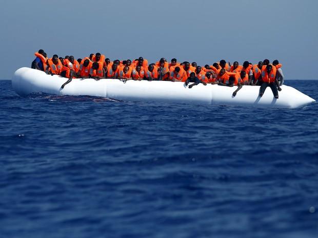 Imigrantes aguardam resgate em um bote de borracha a cerca de 32 km da costa da Líbia. Cerca de 118 imigrantes foram resgatados na manhã desta segunda-feira (3) pelo navio MV Phoenix, o primeiro de financiamento privado a operar no Mediterrâneo (Foto:  Darrin Zammit Lupi/Reuters)