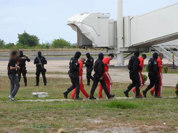 Presos são levados para embarcar em avião (Foto: Jackson Félix/G1 RR)