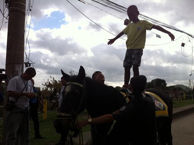 O menino Andrey Felipe Pinheiro, de 8 anos, fica em pé no cavalo da PM, na Favela da Cachoeirinha. O subcomandante do RPMont, tenente coronel Edson Muniz, explica que o cavalo tem a função de integrar os moradores aos policiais militares. (Foto: Tássia Thum/G1)