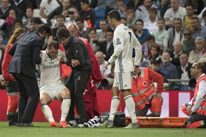 Bale é ajudado depois de sofrer pancada em jogo da Champions (Foto: CURTO DE LA TORRE / AFP)