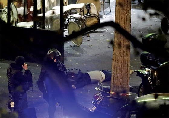 Polícia em Paris ao lado de corpos nas ruas. (Foto: Christian Hartmann/Reuters)