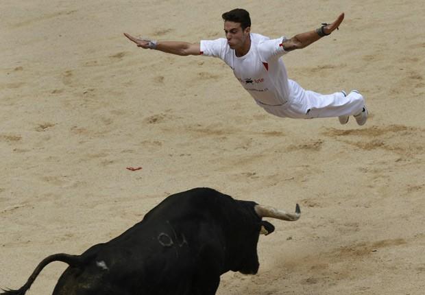 Artista pula sobre touro durante o terceiro dia do Festival de São Firmino, na cidade espanhola de Pamplona (Foto: Joseba Etxaburu / Reuters)