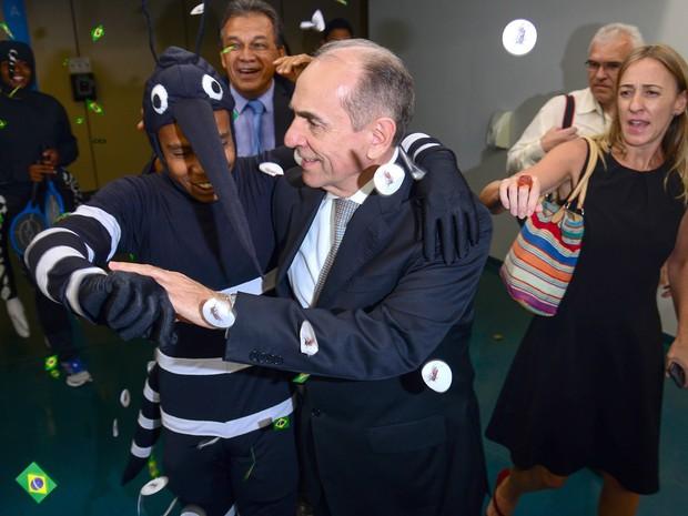 O ministro da saúde Marcelo Castro é cercado por manifestantes fantasiados de mosquito Aedes aegypti ao deixar o plenário da eleição do PMDB na Câmara dos Deputados, em Brasília (Foto: Fabio Pozzebom/Agência Brasil)