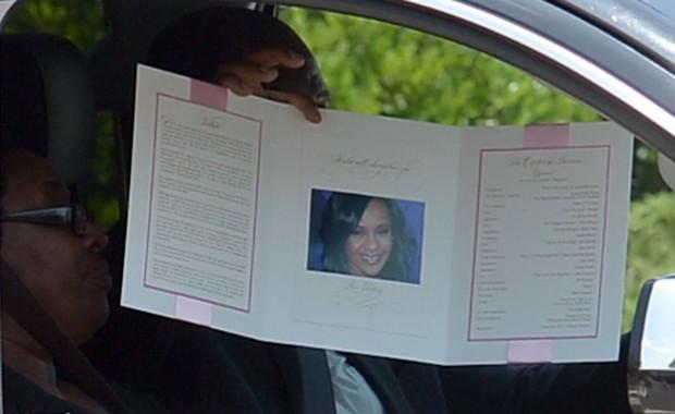 Participante exibe programação do funeral de Bobbi Kristina (Foto: Paras Griffin / GETTY IMAGES NORTH AMERICA / AFP)