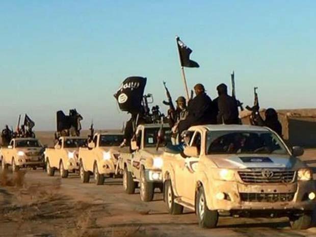 Jihadistas do Estado Islâmico exibem suas armas e bandeiras do grupo em comboio em uma estrada de Raqqa, na Síria, que se dirige ao Iraque (Foto: Militant website via AP)