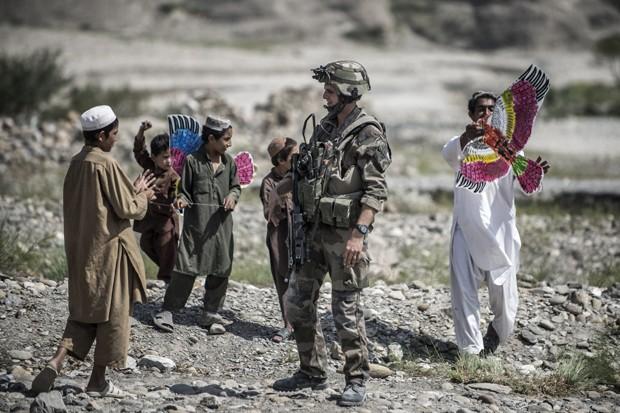 Meninos brincam com as pipas próximos aos soldados  (Foto: JEFF PACHOUD/AFP)