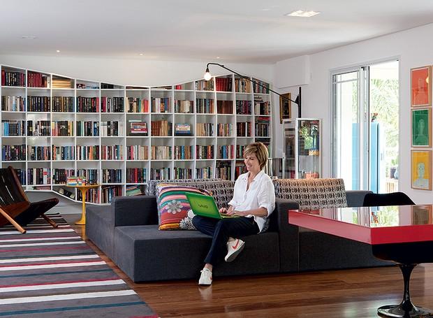 O sofá tem vista para todos os lados na sala da artista plástica Dedéia Meirelles. Dali é possível ver a varanda, a sala de jantar ou a estante Treme-Treme, do coletivo Triptyque, que abriga os livros da família (Foto: Marcos Antonio/Casa e Jardim)