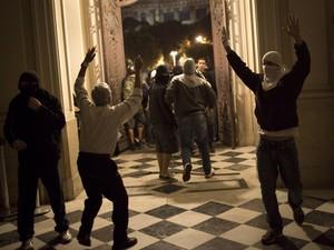 Funcionário da Câmara do Rio tenta conter manifestantes que invadiram local na noite desta quarta-feira (30). (Foto: Felipe Dana/AP)