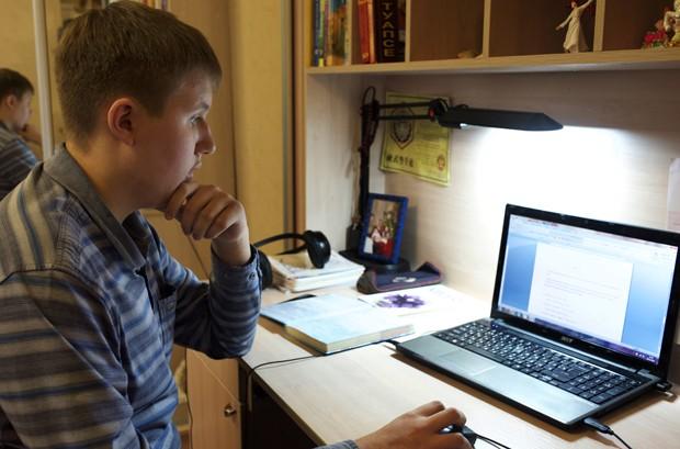 Denis Akimov, de 15 anos, estuda em casa usando o computador em Donestk, na Ucrânia (Foto: Balint Szlanko/AP)