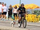Ex-BBB Yuri pedala na orla na companhia de seu cachorro