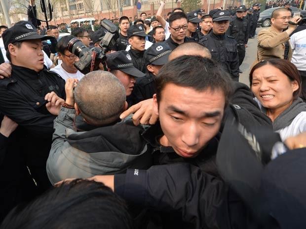 Familiares de passageiros chineses desaparecidos marcham na direção do prédio da Embaixada da Malásia em Pequim. (Foto: Mark Ralston / AFP Photo)