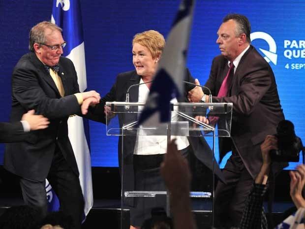 Seguranças retiram Pauline Marois do palco, após ataque durante discurso em Québec. (Foto: Paul Chiasson / The Canadian Press / AP Photo)